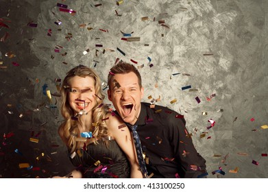 People celebrate holiday with tinsel salute, portrait of young man and woman couple