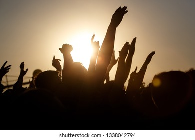 People celebrating on an summer open air. Shillouettes of raised hands