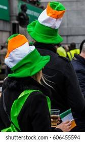 People celebrating St. Patrick day in Trafalgar Square while on stage performing Irish music groups