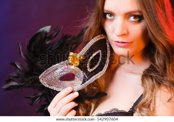 People celebration concept. Masquerade. Beautiful girl holding carnival mysterious mask on dark
