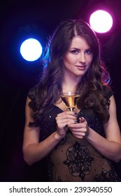 People celebration concept. Sensual woman with glass of cocktail over dark background