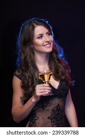 People celebration concept. Smiling woman with glass of cocktail looking away, over dark background