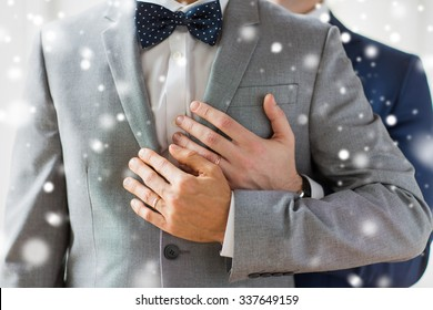 people, celebration, homosexuality, same-sex marriage and love concept - close up of happy male gay couple with wedding rings hugging over snow effect