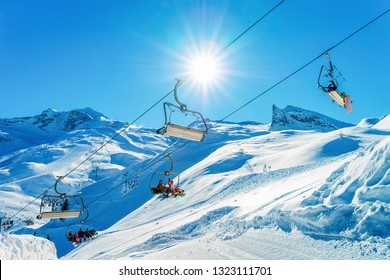 People at Chair lifts at Hintertux Glacier ski resort in Zillertal in Tyrol in Austria in winter in Alps. Chairlifts in Alpine mountains with snow. Downhill fun. Family vacation. White slopes.