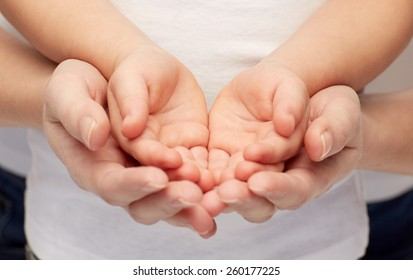 people, charity, family and advertisement concept - close up of woman and girl holding something in empty cupped hands