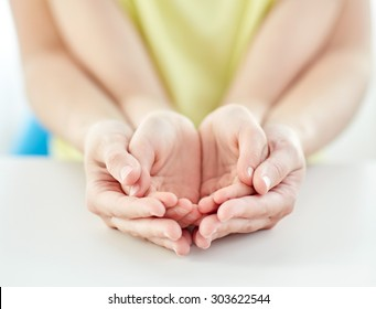 people, charity, family and advertisement concept - close up of woman and girl holding somethining in cupped hands