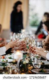 People cheers at the table with glasses of champagne