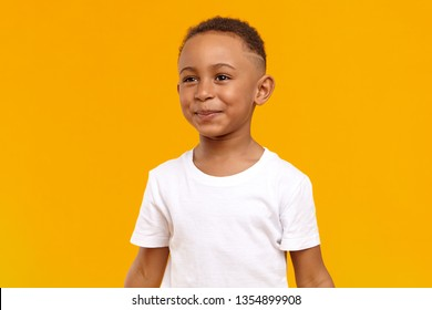 People, childhood, joy and happiness concept. Joyful cheerful Afro American boy of school age having fun, being in good mood, playing after he did his homework, posing isolated at yellow wall