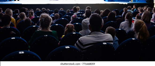 People children and adults in the theatre watching a play