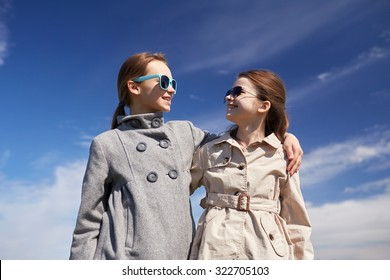 people, children, friends and friendship concept - happy little girls in sunglasses hugging and talking outdoors
