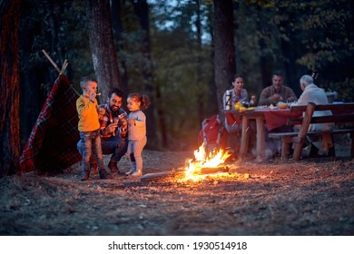 People with children on picnic in wood near campfire
