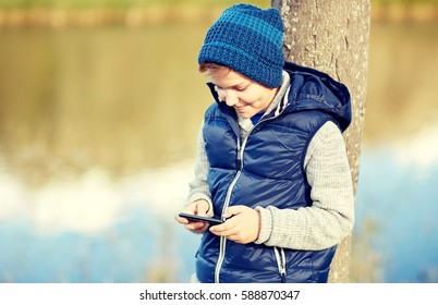people, children and technology concept - happy teenage boy playing game or texting message on smartphone outdoors