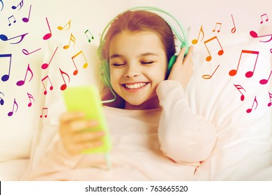 people, children and technology concept - happy smiling girl with smartphone and headphones lying in bed listening to music over musical notes