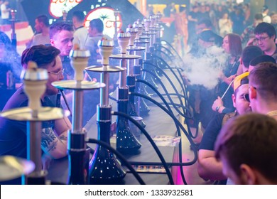 People choose hookah. Smoke. People looking at samples of tobacco. Smoking accessories. Tabaka. Hookah Club Show. Exhibition of hookahs. 9.3.2019. Russia. Saint Pete