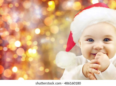 people, christmas, children and holidays concept - happy baby in santa hat over lights background