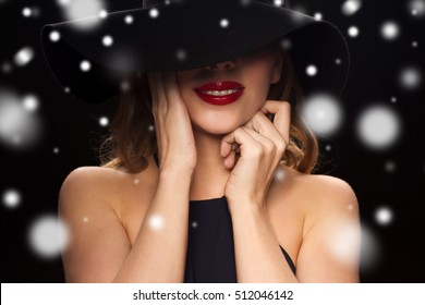 people, christmas, holidays, luxury and fashion concept - beautiful woman in hat over black background and snow