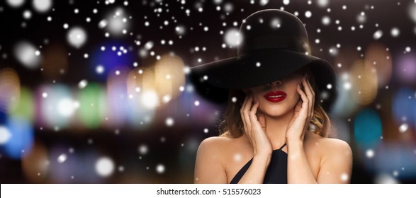 people, christmas, holidays, luxury and fashion concept - beautiful woman in black hat over blurred night lights background and snow