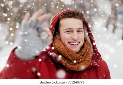 people, christmas, winter and season concept - happy smiling man in hood and scarf outdoors showing ok hand sign