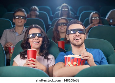People at the cinema. Cheerful people in three-dimensional glasses watching movie at the cinema