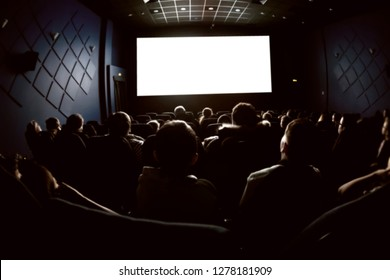 People in the cinema watching a movie. Blank empty white screen. Blurred image