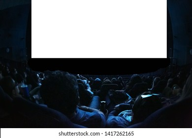 People in the cinema watching a movie. Blank empty white screen. Leisure entertainment concept.