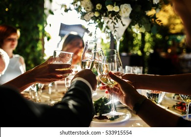 People clang glasses sitting at dinner table illuminated with evening lights