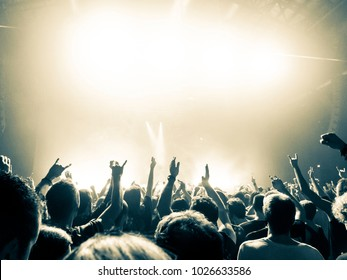 People clapping in front of a big concert stage