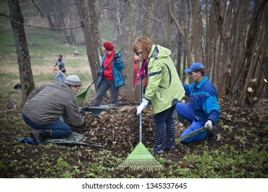 People clean fallen leaves. Public cleaning of municipal territories in Rezekne - Latvia, April 2016.