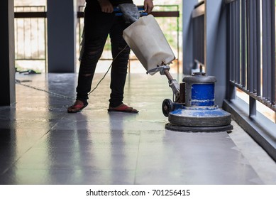 The people cleaning floor with machine.