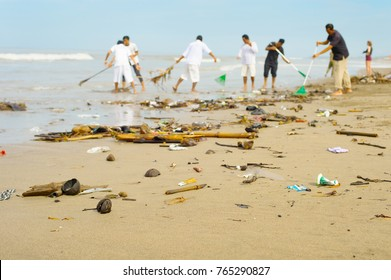 People cleaning trashy polluted with garbage ocean beach. Bali island, Indonesia
