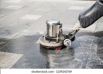 The people cleaning wash exterior walkway using polishing machine.