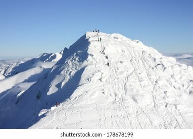 People climbing Chopok Peak, 2024 m, on a bright day