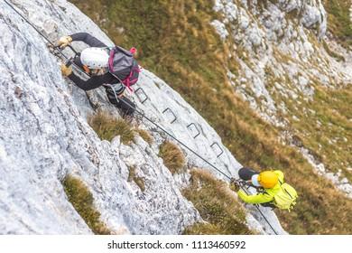 People climbing on steep rock face on via ferrata. Climbers on via ferrata climbing route. Alpine ferrata ascent to a peak or summit. Summer adventure mountain sport activity in alpine landscape.