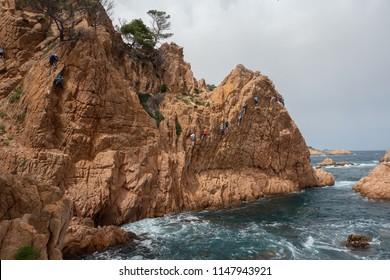 People climbing on Via Ferrata Cala de Molí (Sant Feliu de Guixols, Catalonia, Spain)
