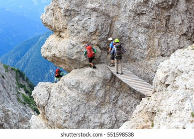 People climbing the Via Ferrata Severino Casara with bridge in Sexten Dolomites mountains, South Tyrol, Italy