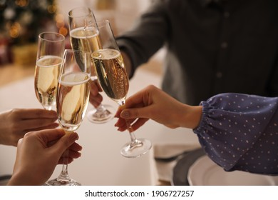 People clinking glasses with champagne at home, closeup