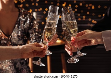 People clinking glasses of champagne indoors, closeup