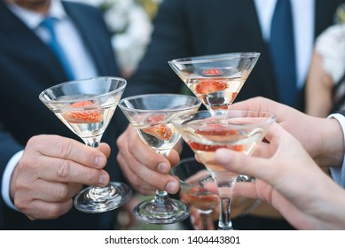 people clinking glasses of champagne with strawberry