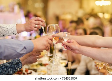 people clinking glasses with each other, glasses with alcohol and toasting, party,people, leisure and drinks concept Close up of male hands clinking glasses with alcohol and pretzels at bar or pub