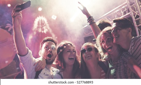 People clubbing and dancing at party during festival