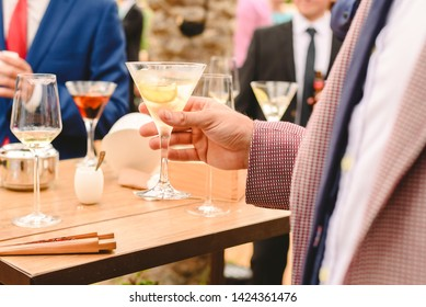 People in a cocktail drinking alcohol from their glasses and having fun at the party.