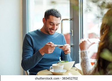 people, communication and dating concept - happy couple with smartphones picturing food at cafe or restaurant