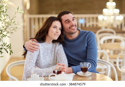 people, communication and dating concept - happy couple drinking tea and hugging at cafe or restaurant