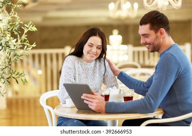 people, communication and dating concept - happy couple with tablet pc computer at cafe or restaurant