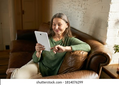 People, communication, electronic gadgets and devices. Beautiful woman pensioner relaxing on comfortable leather sofa with digital tablet, playing video games or chatting online via social networks