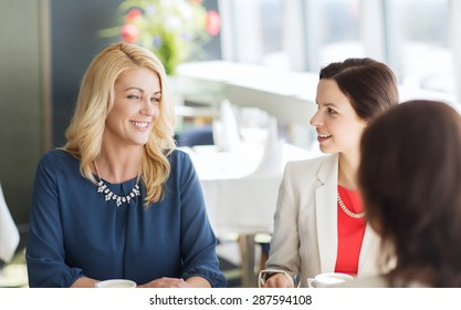 people, communication and lifestyle concept - happy women drinking coffee and talking at restaurant