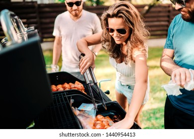 People concept - Friends having a barbecue party in nature while having a good time, drinking, cooking and eating