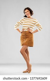 people concept - happy smiling young woman in striped pullover, short skirt and ballet flat shoes with hands on hips posing over grey background