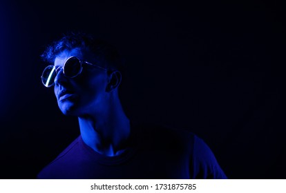 People concept. Portrait of young man in glasses. Dark background. Fashion male. Guy. Sunglasses. Party. Fit. Motivation. Lights. Portrait. Night. Fashion photo. Posing studio. Lamp.