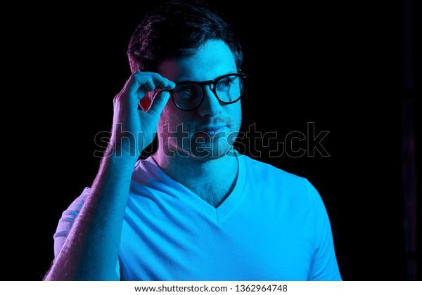 concepto de la gente - retrato de un joven con gafas y pantalones sobre luces de neón ultra violeta en habitación oscura